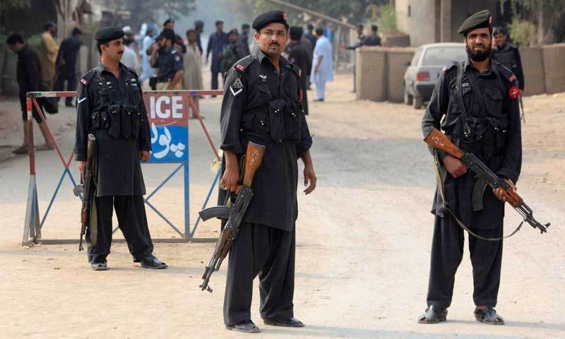 Policemen stand guard at a checkpoint after it was attacked by a hand grenade in the outskirts of Peshawar
